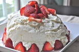 Angel food cake with lemon whipped cream frosting and strawberries